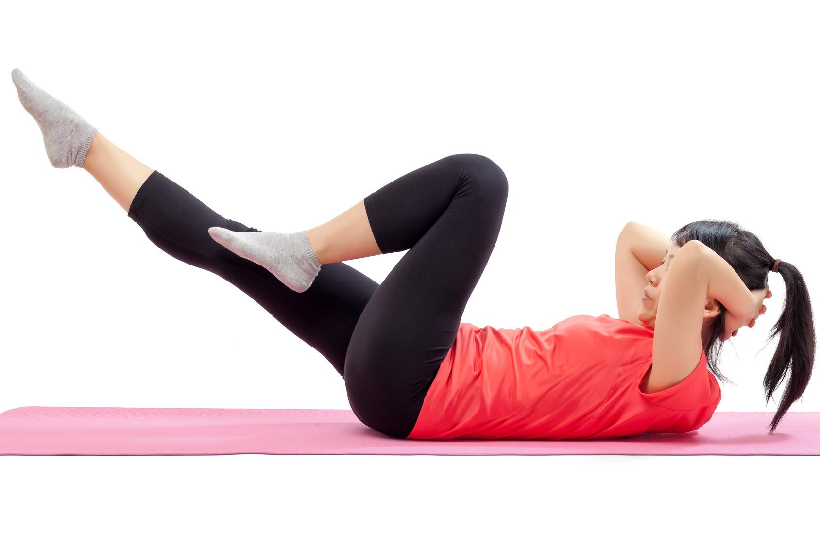 Woman doing abdominal exercises isolated on white background